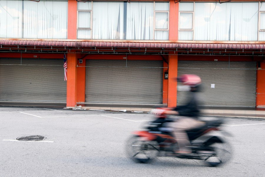 A motorcyclist rides pass lines of closed shops amid the Movement Control Order. - BERNAMA pic