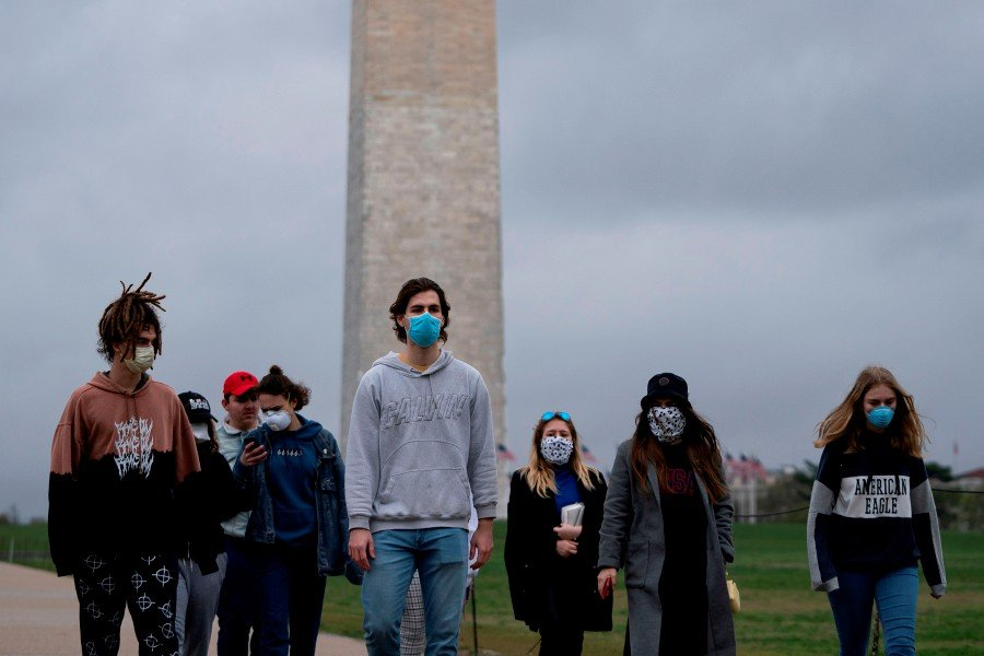 A group of young people wear protective masks as they walk near the Washington Monument on the National Mall on March 25, 2020, in Washington. - AFP pic