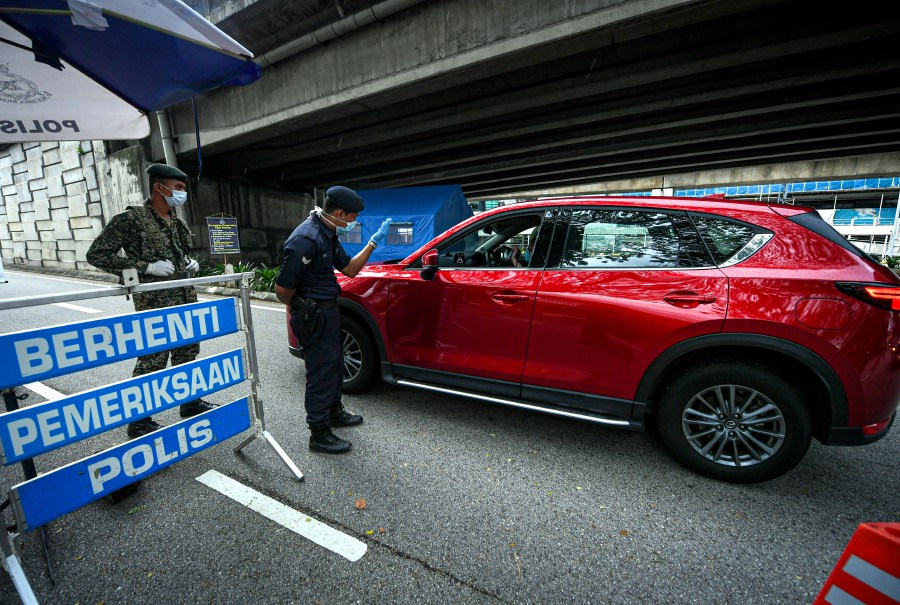 A policeman and a soldier stand guard during a roadblock in Kuala Lumpur, amid the Movement Control Order. - BERNAMA pic