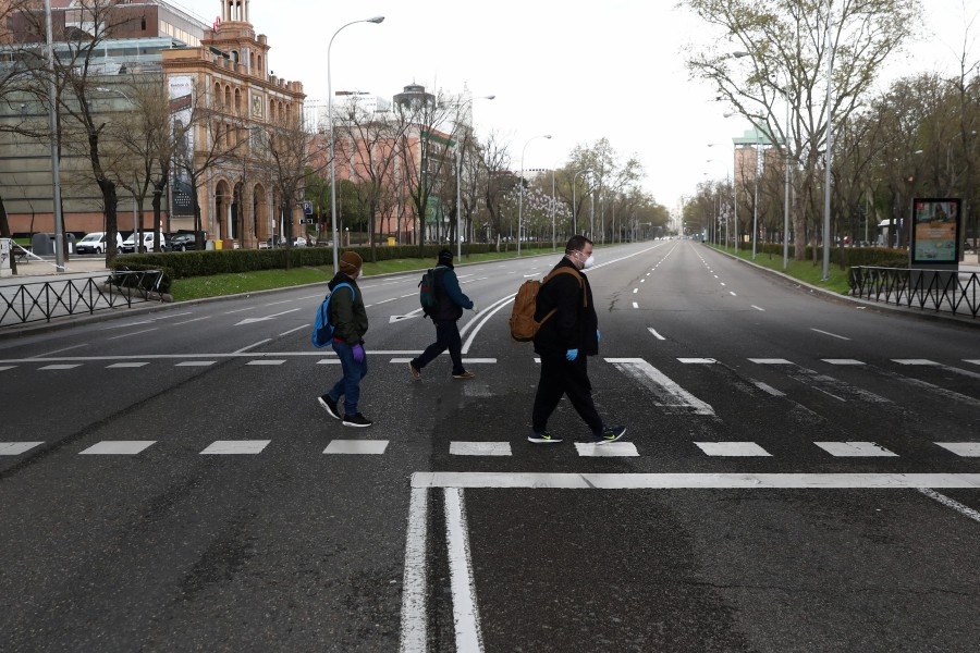 People wearing protective face masks keep social distancing as they cross an almost deserted Paseo de la Castellana street during the coronavirus disease (COVID-19) outbreak, in Madrid. - REUTERS pic
