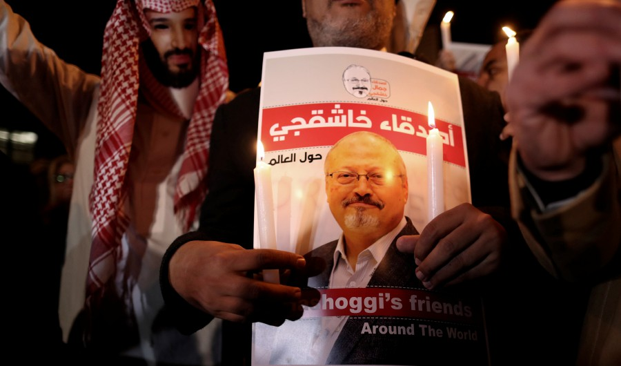 A protestor (left) wears a mask of Saudi Crown Prince Mohammad Bin Salman with a red painted hands while others hold images of Saudi journalist Jamal Khashoggi during a demonstration in front of Saudi Arabian consulate in Istanbul, Turkey, October 25, 2018. - EPA
