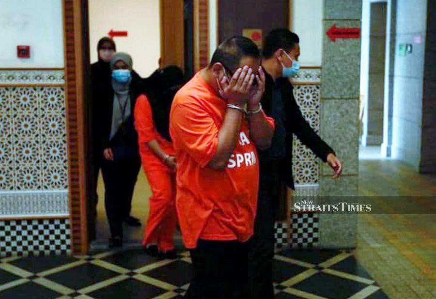 This Nov 27 pic shows three Immigration Dept officers being led by MACC officers at the Putrajaya Courts Complex.