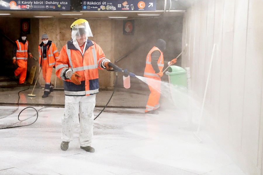 Workers wearing protective suits clean and disinfect an underpass to prevent the spread of coronavirus disease (COVID-19), in downtown Budapest, Hungary. - AFP pic