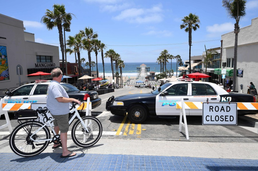 A man wearing a mask looks out over a road closed to auto traffic near the pier in Manhattan Beach, California where beaches are closed due to a spike in COVID-19 in Los Angeles County, on July 4, 2020, the US Independence Day holiday. - AFP pic