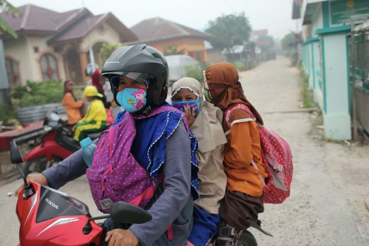 A parent taking her children home after the Air Pollutant Index (API) for Riau was at a worrying state, and schools in the province were ordered to close by the Indonesian authorities. Pix by Ghazali Kori