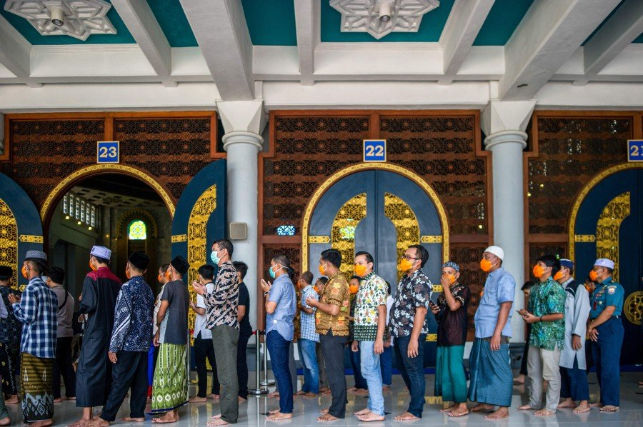 People wearing face masks as a precaution against the COVID-19 coronavirus outbreak attend obligatory Friday prayers at a mosque in Surabaya, East Java. -AFP pic