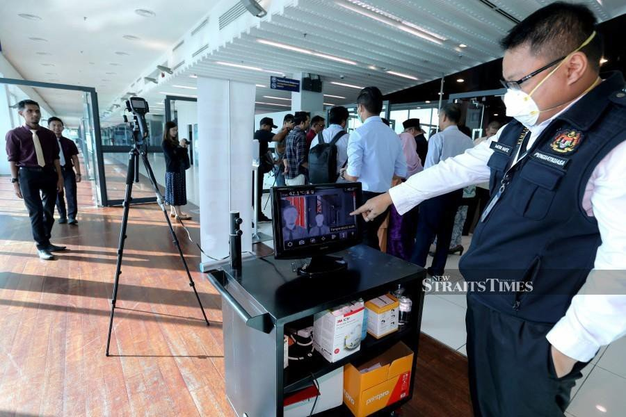 A Health Ministry staff observes a thermal scanner installed at Senai International Airport on Jan 22. - NSTP/Zain Ahmed