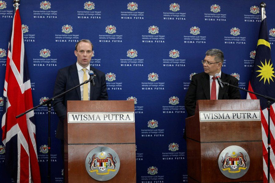 Britain's foreign secretary Dominic Raab speaks as Malaysia's Foreign Minister Datuk Saifuddin Abdullah listens during a joint news conferencein Putrajaya. -Reuters