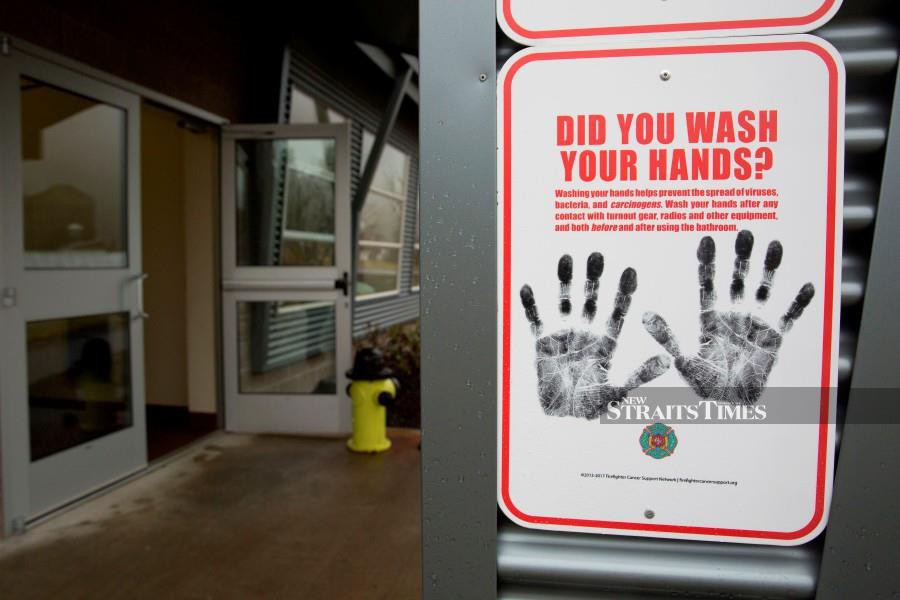 A sign reminding people to wash their hands is pictured outside a dormitory at the Washington State Patrol Fire Training Academy which has been designated as a 2019 novel coronavirus quarantine site for travelers from Hubei Province, China who have been exposed, are not yet symptomatic and cannot self-quarantine, in North Bend, Washington. - AFP