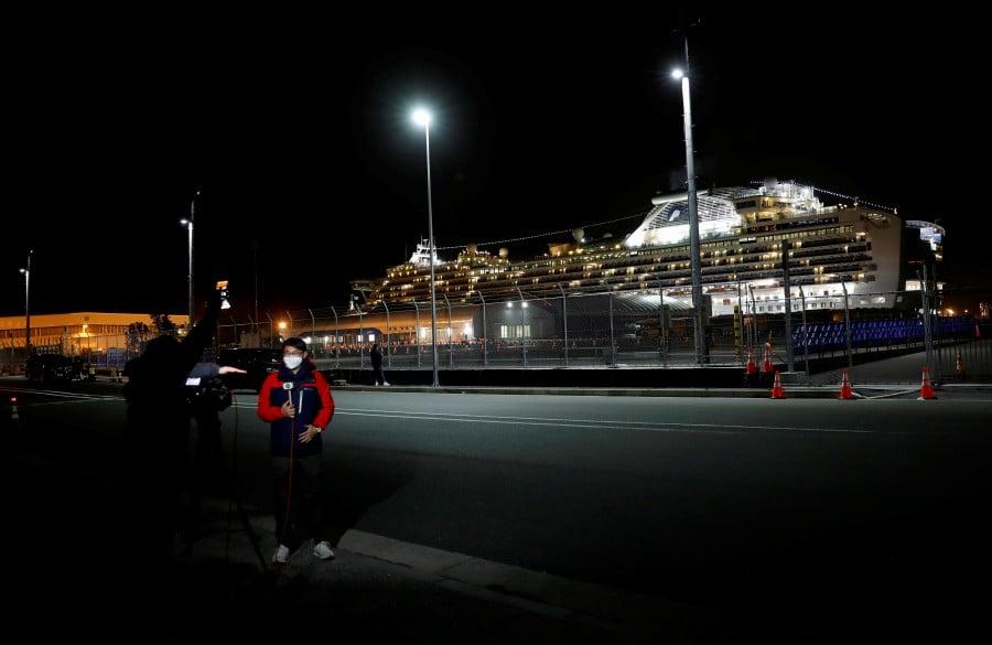 Reporters stand near the cruise ship Diamond Princess, at Daikoku Pier Cruise Terminal in Yokohama, south of Tokyo, Japan. -Reuters