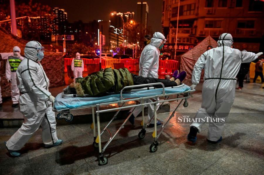 Medical staff members wearing protective clothing to help stop the spread of a deadly virus which began in the city, arrive with a patient at the Wuhan Red Cross Hospital in Wuhan. -AFP