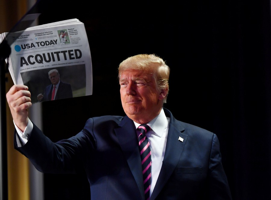 """US President Donald Trump holds up a newspaper that displays a headline """"Acquitted"""" as he arrives to speak at the 68th annual National Prayer Breakfast on February 6, 2020 in Washington, DC. - AFP"""