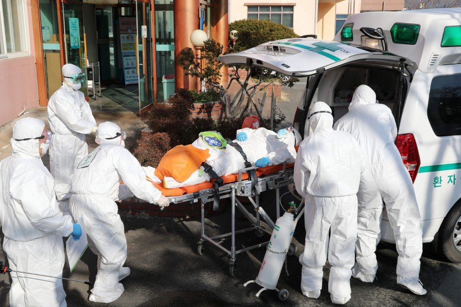 Medical workers wearing protective gear transfer a suspected coronavirus patient (centre) to another hospital from Daenam Hospital where a total of 16 infections have now been identified with the COVID-19 coronavirus, in Cheongdo county near the southeastern city of Daegu. -YONHAP/AFP