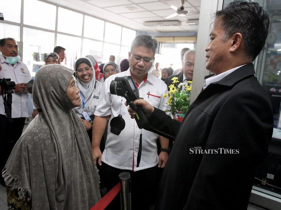 This file pic dated Jan 15, shows Kelantan Health director Datuk Dr Zaini Hussin (right) using a special screening equipment on a passenger at the Customs, Immigration and Quarantine Complex in Rantau Panjang. - NSTP/File pic