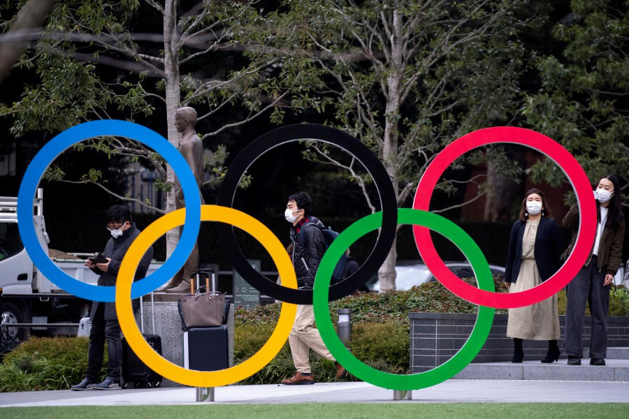 People wearing protective face masks, following an outbreak of the coronavirus, are seen next to the Olympic rings in front of the Japan Olympic Museum in Tokyo, Japan. -Reuters