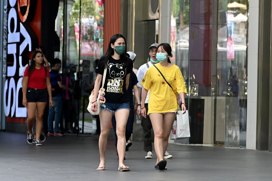 People wearing protective facemasks amid fears about the spread of the COVID-19 coronavirus walk past a shopping mall in Singapore. -AFP