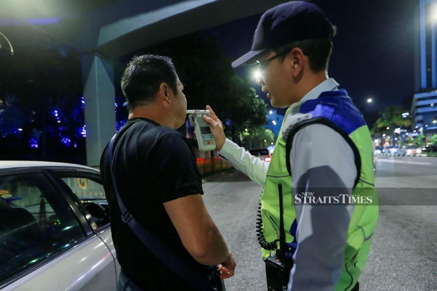 This file pic dated Dec 25, 2018, shows a traffic policeman using a breathalyser during a road block in Jalan Kampung Pandan. -NSTP/File pic