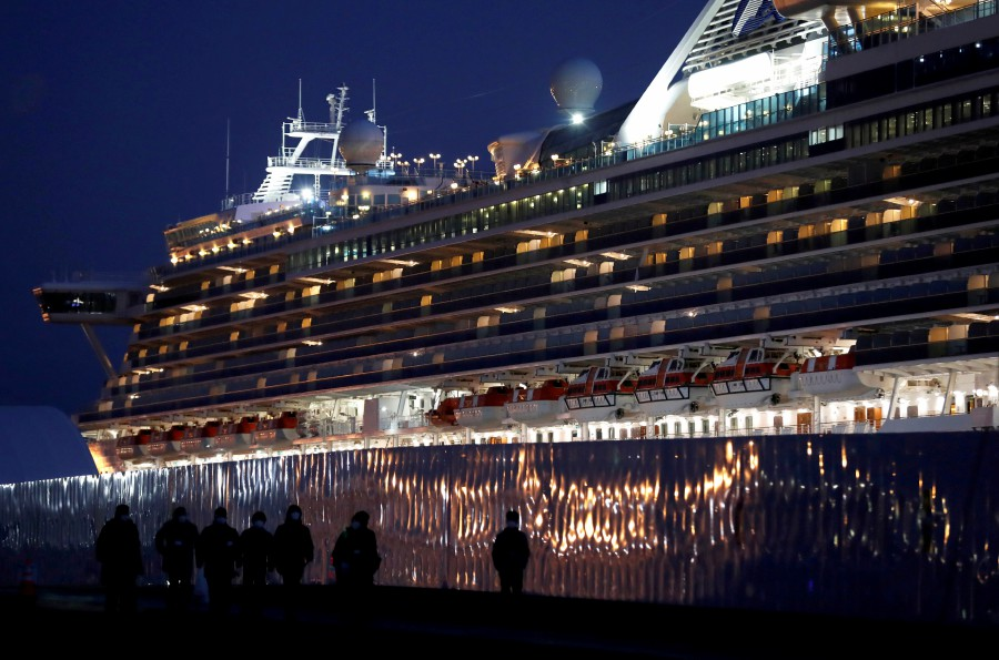 Workers walk past the coronavirus-hit cruise ship Diamond Princess as they leave the Yokohama Port, south of Tokyo, Japan on February 21. - Reuters/File pic