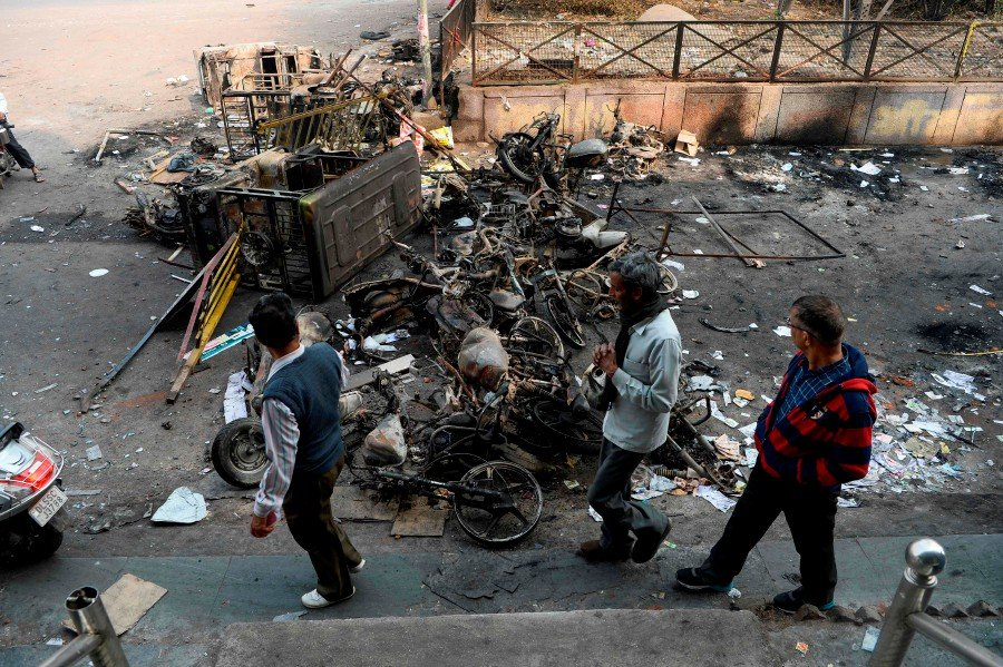 Men make their way around burnt-out vehicles following clashes between people supporting and opposing a contentious amendment to India's citizenship law, in New Delhi. -AFP