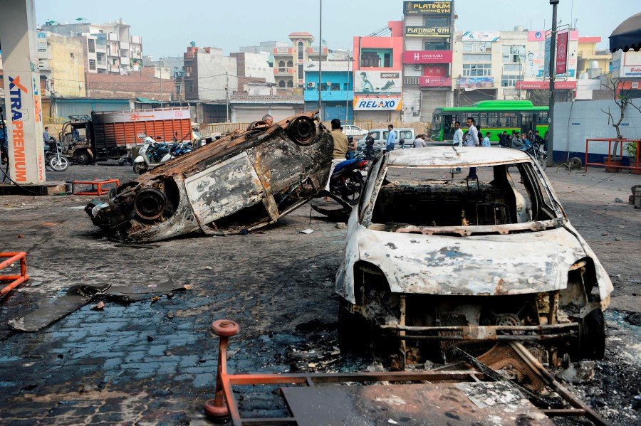 Local residents look at burnt-out vehicles following clashes between people supporting and opposing a contentious amendment to India's citizenship law, in New Delhi. -AFP