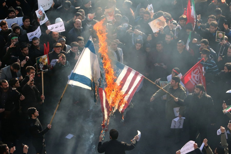 Iranians set a US and an Israeli flag on fire during a funeral procession organised to mourn the slain military commander Qasem Soleimani, Iraqi paramilitary chief Abu Mahdi al-Muhandis and other victims of a US attack in the capital Tehran. -AFP