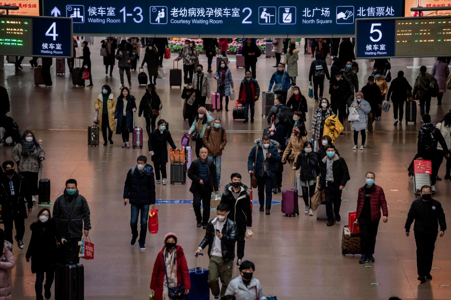 People wearing protective masks travel for the Lunar New Year holidays at the Beijing West Railway Station in Beijing. -AFP