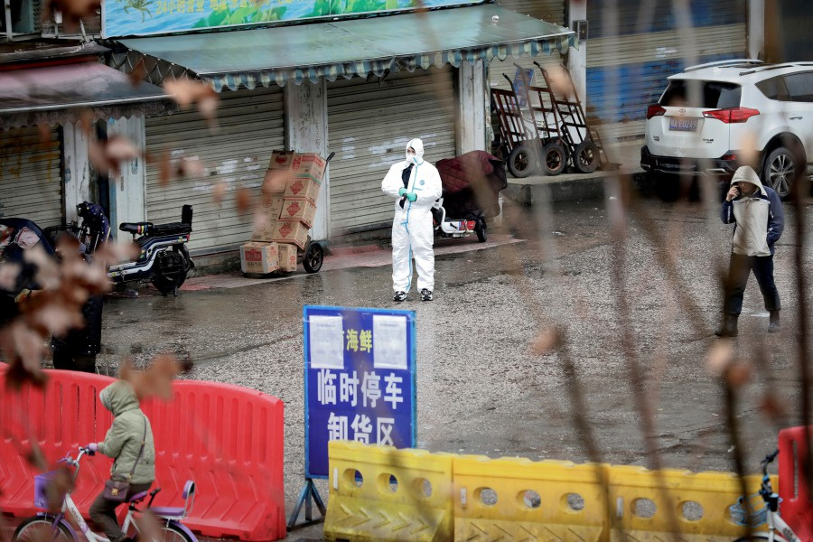 A worker in a protective suit is seen at the closed seafood market in Wuhan, Hubei province, China. -Reuters