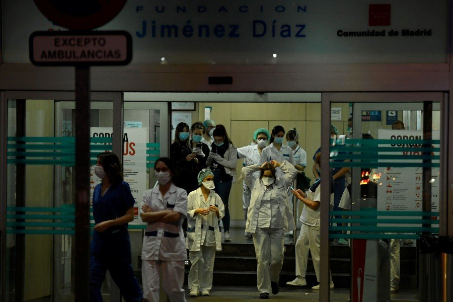 Healthcare workers dealing with the new coronavirus crisis stand at the entrance of the Fundacion Jimenez Diaz hospital in Madrid. - AFP pic