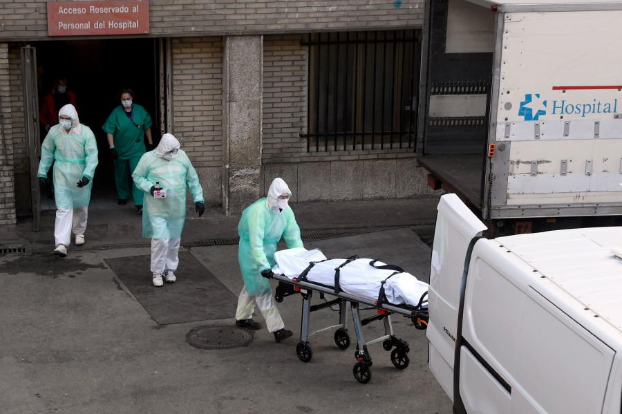 A health worker carries a body on a stretcher outside Gregorio Maranon hospital in Madrid. - AFP pic