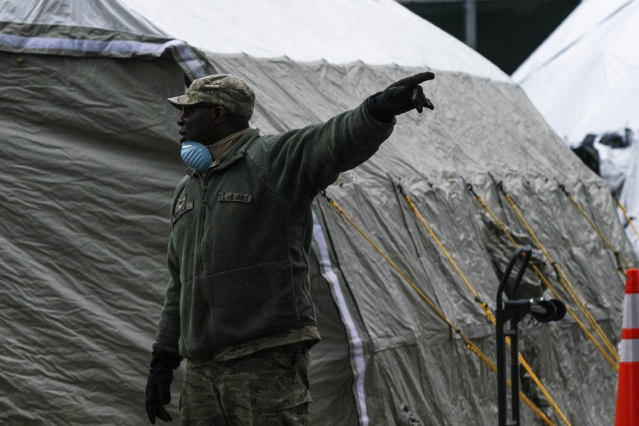 An Air Force member gives instructions as workers and Military Members build a makeshift morgue outside of Bellevue Hospital on March 25, 2020 in New York City, New York. -AFP pic