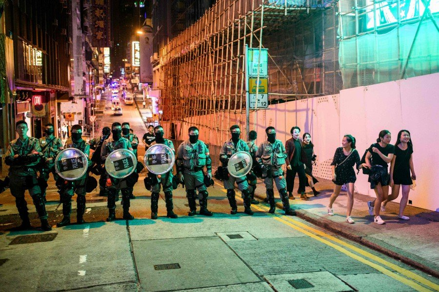 A group of revellers (right) walk past a line of riot police as they block entry to the Lan Kwai Fong area during Halloween in Hong Kong. - AFP