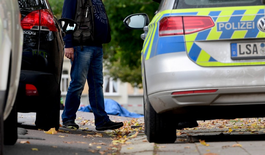 A police officer passes the covered body of a dead person at a Synagogue after a shooting in Halle, Germany. - EPA