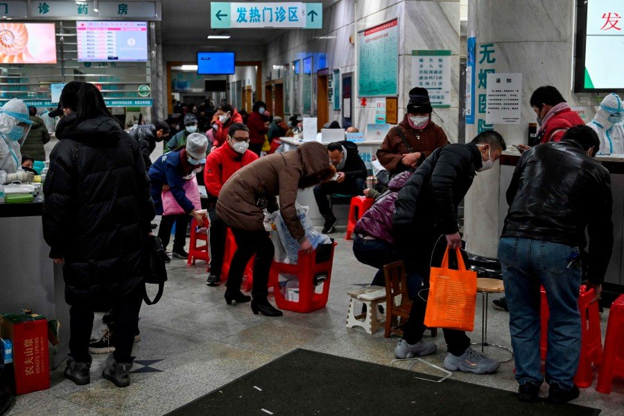 People wearing facemasks to help stop the spread of a deadly virus which began in the city, wait for medical attention at Wuhan Red Cross Hospital in Wuhan. -Reuters
