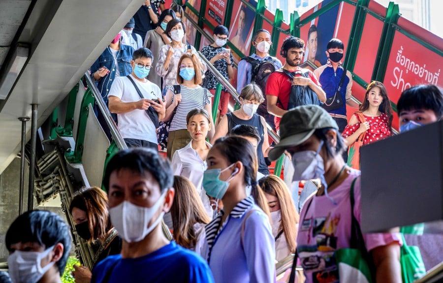 People with face masks arrive at a BTS Sky train station in Bangkok. -AFP
