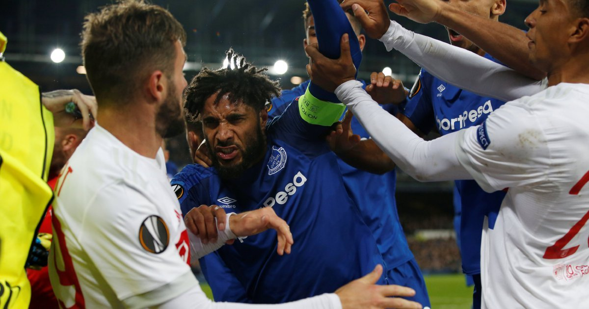 Everton fan holding child punches Lyon player