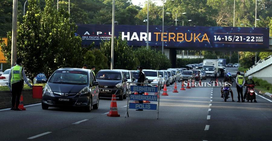 Police officers manning a roadblock in Kuala Lumpur amid the Movement Control Order.- NSTP/HAIRUL ANUAR RAHIM