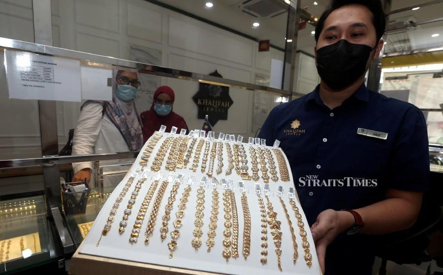 Khalifah Jewels Shah Alam branch manager Mohd Faiz Mohd Taib displays some of the gold jewellery on offer at the store. NSTP/HAIRUL ANUAR RAHIM.