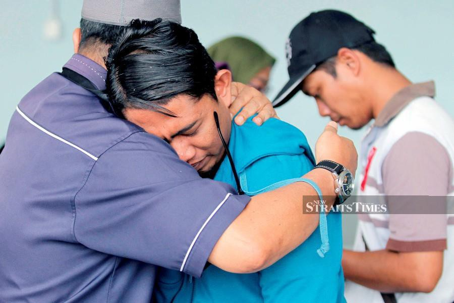 Family members of victims comfort each other at the Forensic Unit of the Sepang Hospital. - NSTP/AIZUDDIN SAAD