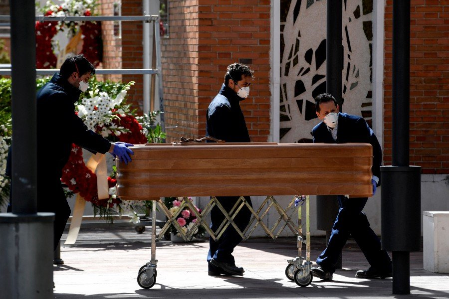 Mortuary employees wearing face masks wheel a coffin into the crematorium of La Almudena cemetery in Madrid on March 24, 2020 during the funeral of a COVID-19 coronavirus victim. - AFP pic