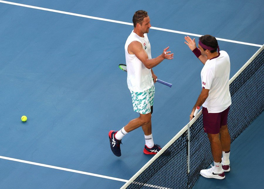 Switzerland's Roger Federer shakes hands with Tennys Sandgren of the USafter winning the match. -Reuters