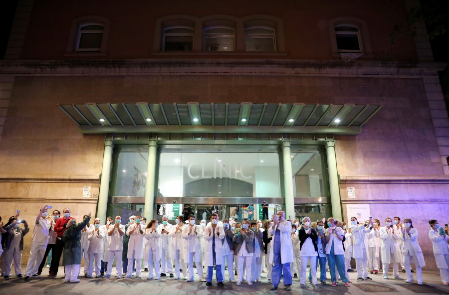 Health workers from Clinic hospital applaud citizens who show them gratitude from their balconies and windows, during the coronavirus disease (COVID-19) outbreak, in Barcelona. - REUTERS pic
