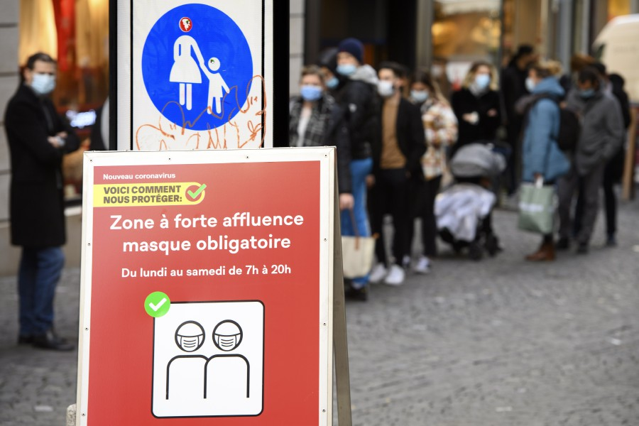 People wearing protective face masks queue outside a Louis Vuitton boutique store for their Christmas shopping during the coronavirus disease outbreak, in Lausanne, Switzerland. - EPA pic