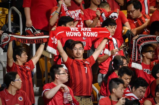 """This photograph taken on September 8, 2015 shows Hong Kong football fans during the 2018 World Cup football qualifying match between Hong Kong and Qatar in Hong Kong. The Hong Kong Football Association (HKFA) said they would be """"disappointed"""" if FIFA punished them after fans jeered the Chinese national anthem before their World Cup qualifier against Qatar. AFP PHOTO"""