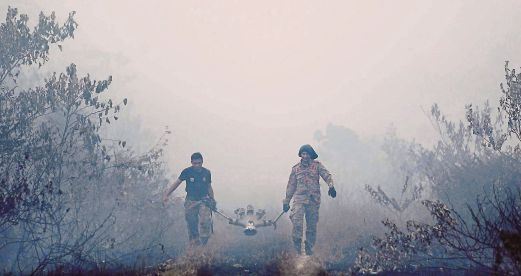 (File pix) Firemen carrying their equipment into the bushes to put out a peat fire near a highway in Sepang in 2014. Pix by Sairien Nafis