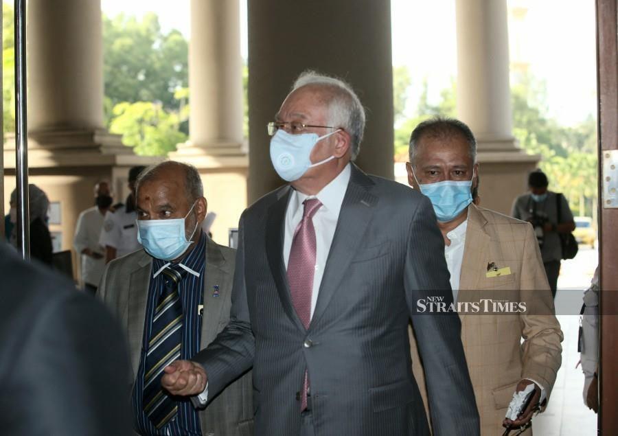 Datuk Seri Najib Razak gestures as he arrives at the court ahead of the trial. -NSTP/EIZAIRI SHAMSUDIN