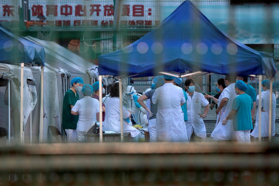 Medical workers wearing protective suit are seen at the Dongdan sports center to collect swab testing to detect the COVID-19 novel coronavirus in Beijing on June 16. - AFP pic