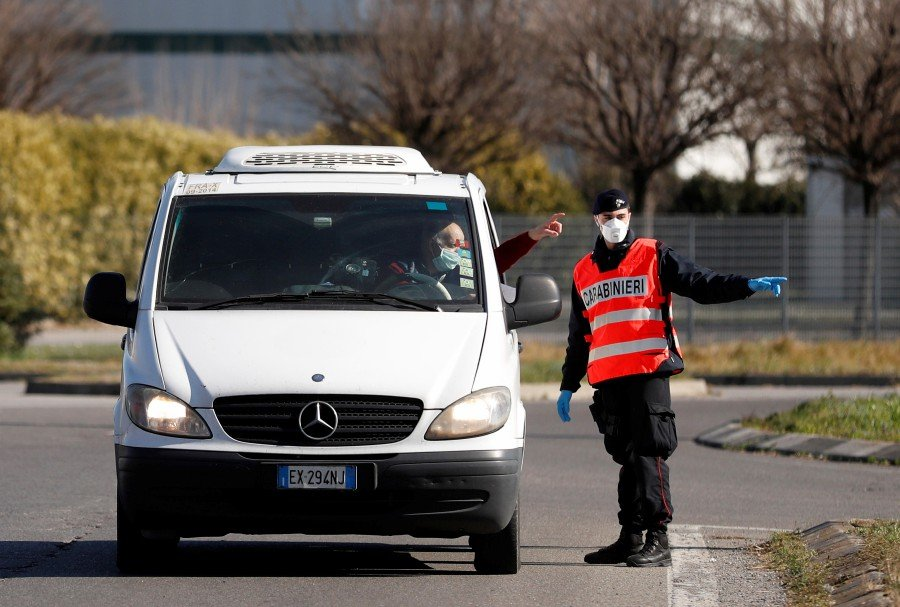A member of the Italian Carabinieri wearing a face mask guides a driver at the entrance of the red zone of Casalpusterlengo, closed off due to a coronavirus outbreak in northern Italy. REUTERS