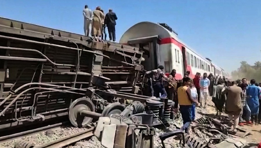This screengrab provided by AFPTV shows people gathered around the wreckage of two trains that collided in the Tahta district of Sohag province, some 460 kms (285 miles) south of the Egyptian capital Cairo. - AFP pic