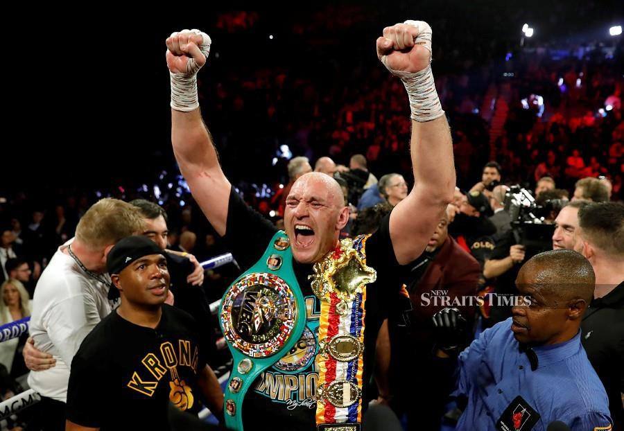 Tyson Fury celebrates with the belts after winning the fight against Deontay Wilder as referee Kenny Bayless looks on. REUTERS pic
