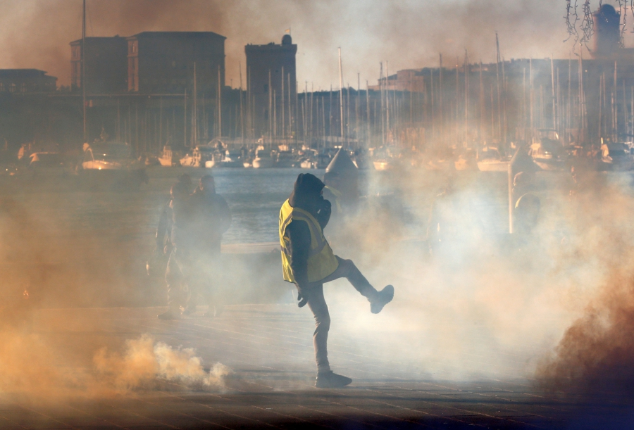 """A yellow vest protester walks among tear gas during clashes with French Gendarmes at a demonstration of the """"yellow vests"""" movement in Marseille, France, December 8, 2018. (REUTERS/Jean-Paul Pelissier)"""